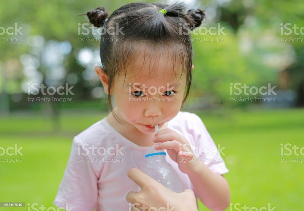 Close Up little girl drinking water in the park. Portrait outdoor. royalty-free stock photo
