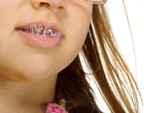 close up little girl in glasses doing fun saliva bubbles - human saliva stock pictures, royalty-free photos & images