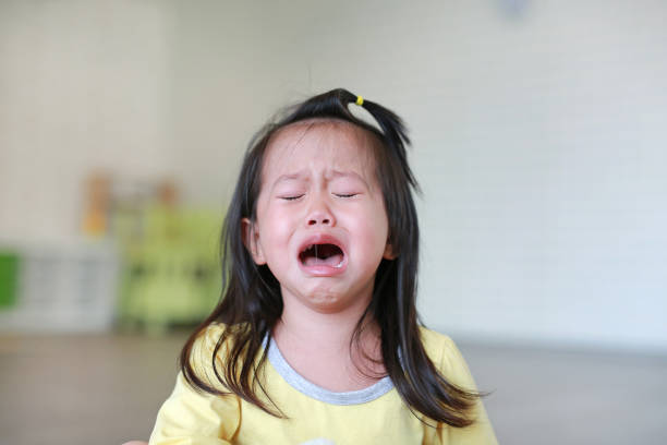 Close up Little kid girl crying with tearful on her face. stock photo