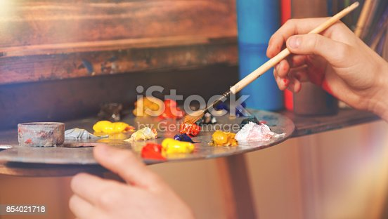 624112404istockphoto Close up look on hand of child mixing oil paints 854021718