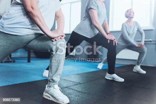 936573360 istock photo Close up look on retired women lunging at fitness club 936573360