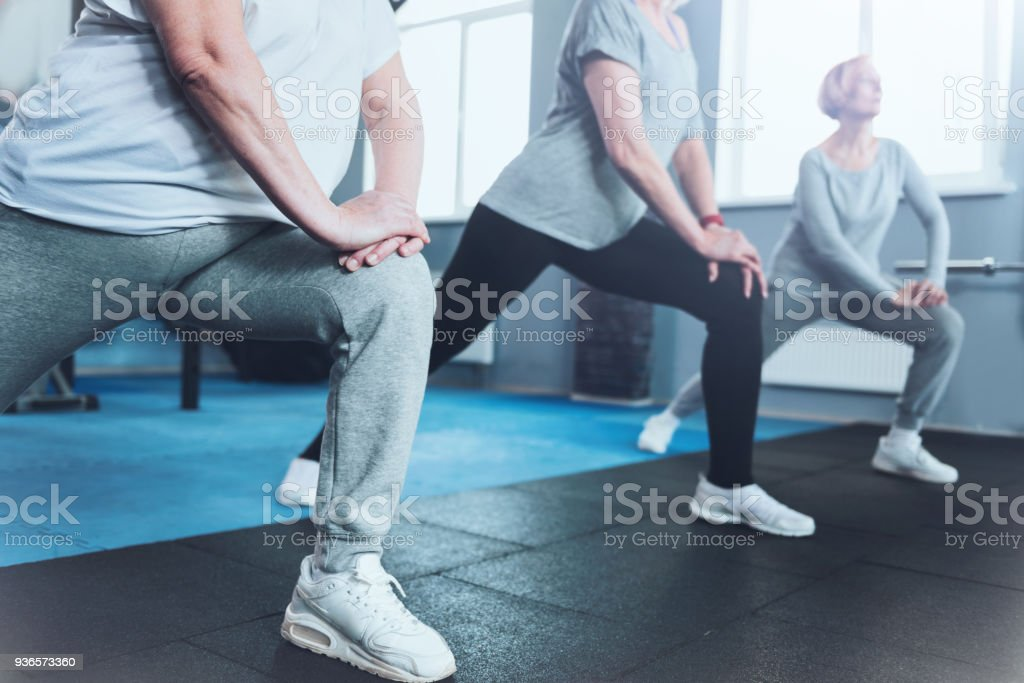 Close up look on retired women lunging at fitness club stock photo