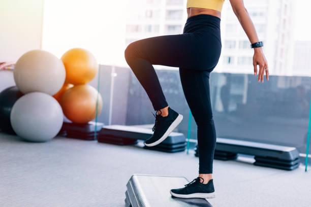 cerca de joven haciendo ejercicios aeróbicos de baja sección. modelo de fitness femenino fresco en el gimnasio con espacio de copia - aeróbic fotografías e imágenes de stock