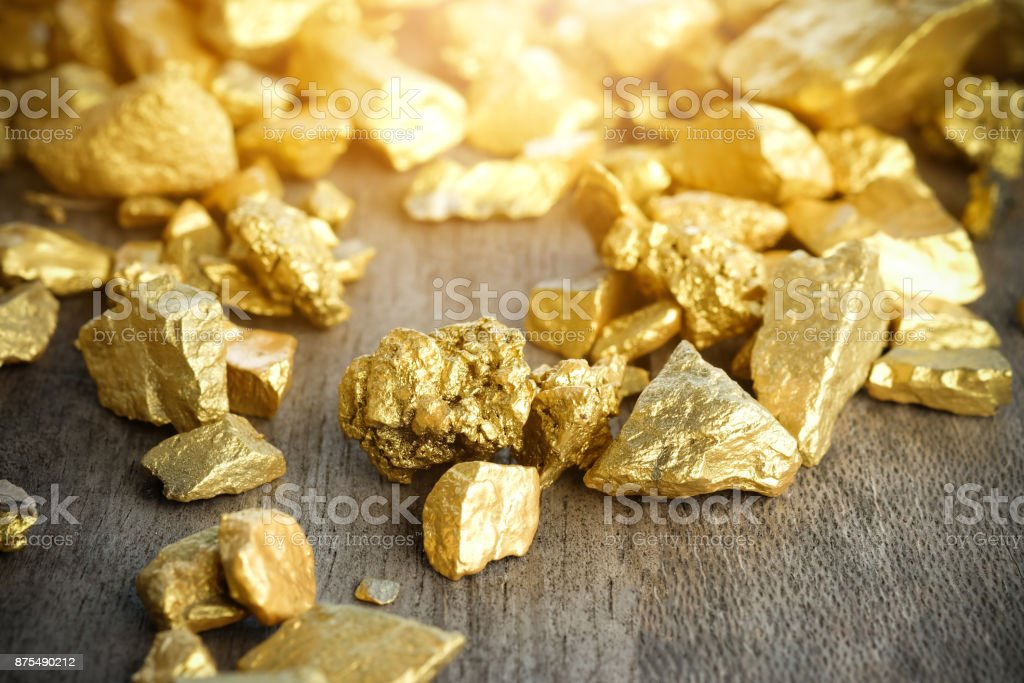 Close up lump of gold mine on wooden table stock photo