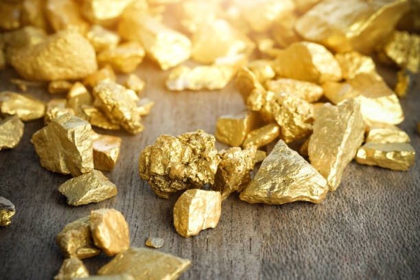 close up lump of gold mine on wooden table - gold mine stock photos and pictures