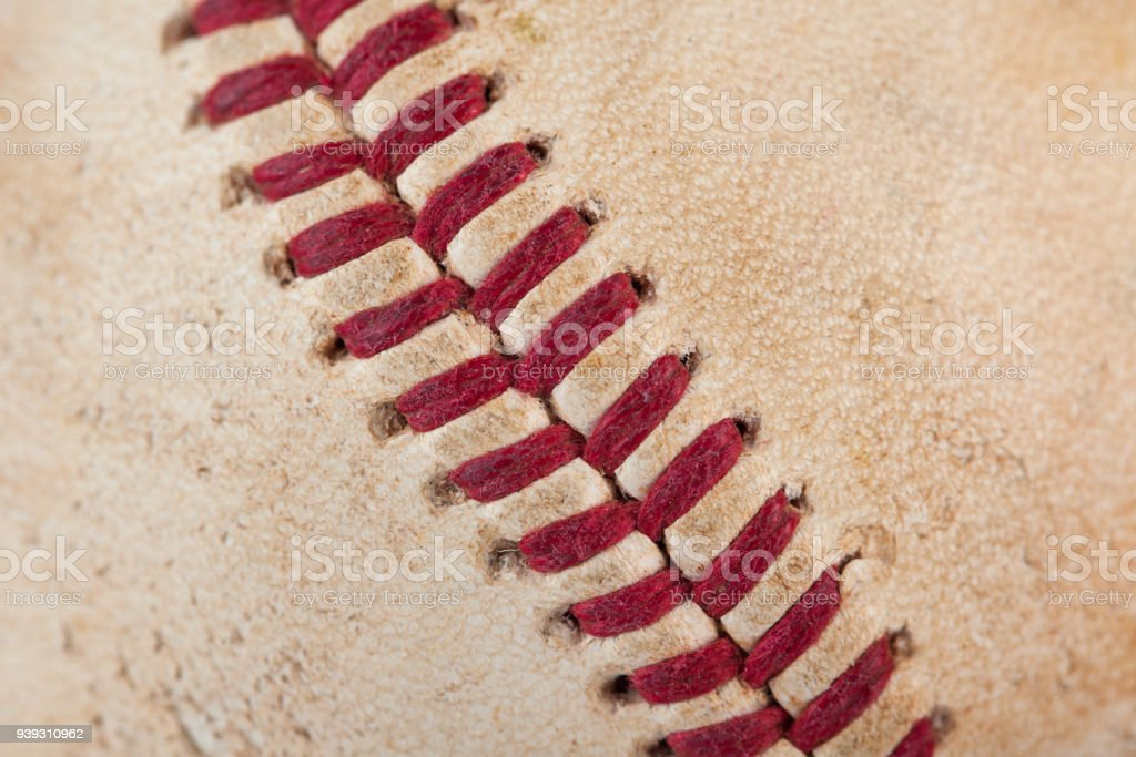 Close up macro view of red stitched seams of an worn baseball stock photo