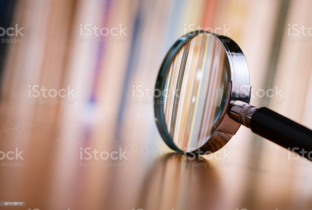 Close up Magnifying Glass Leaning on Wooden Table stock photo