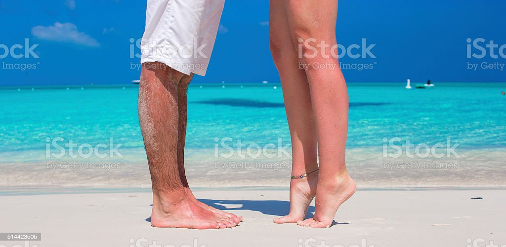 Close up male and female feet on white sand stock photo