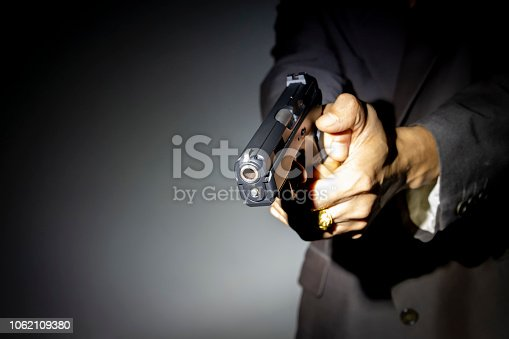 Close up male hand holding gun for shooting