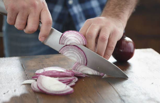 close up male hands chopped fresh red onion on wooden table - alliacee foto e immagini stock
