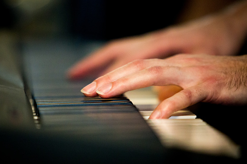 Close up male hands playing electric piano