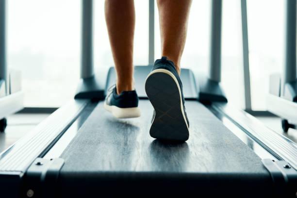 Nahaufnahme männlichmuskuläre Füße in Turnschuhen läuft auf dem Laufband im Fitnessstudio – Foto