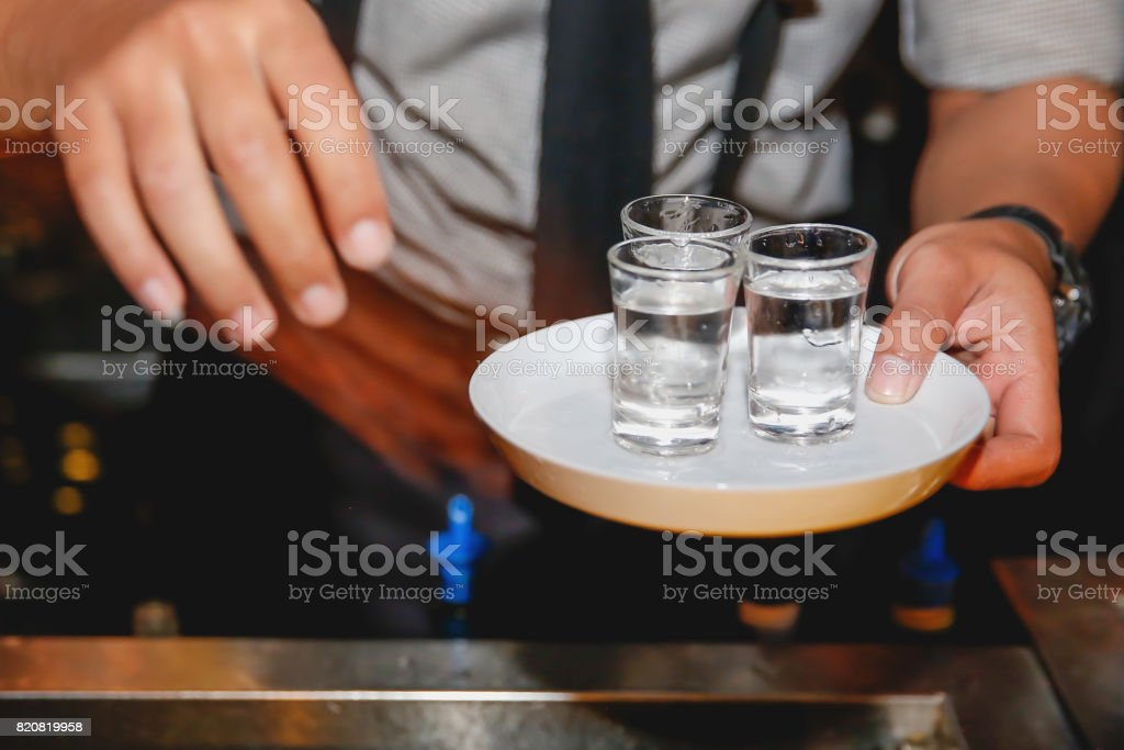 Close up males bartender preparing tequilla shots stock photo