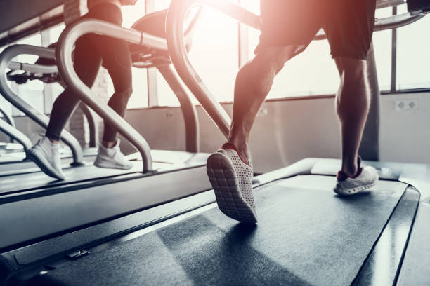 Close up. Man and Young Woman on Treadmills in Gym stock photo