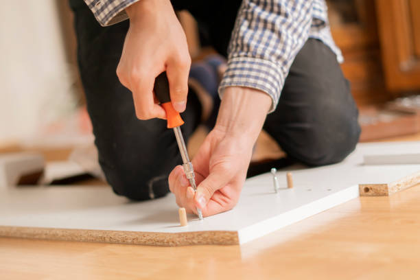 close up man assembling new furniture with a screwdriver b stock photo