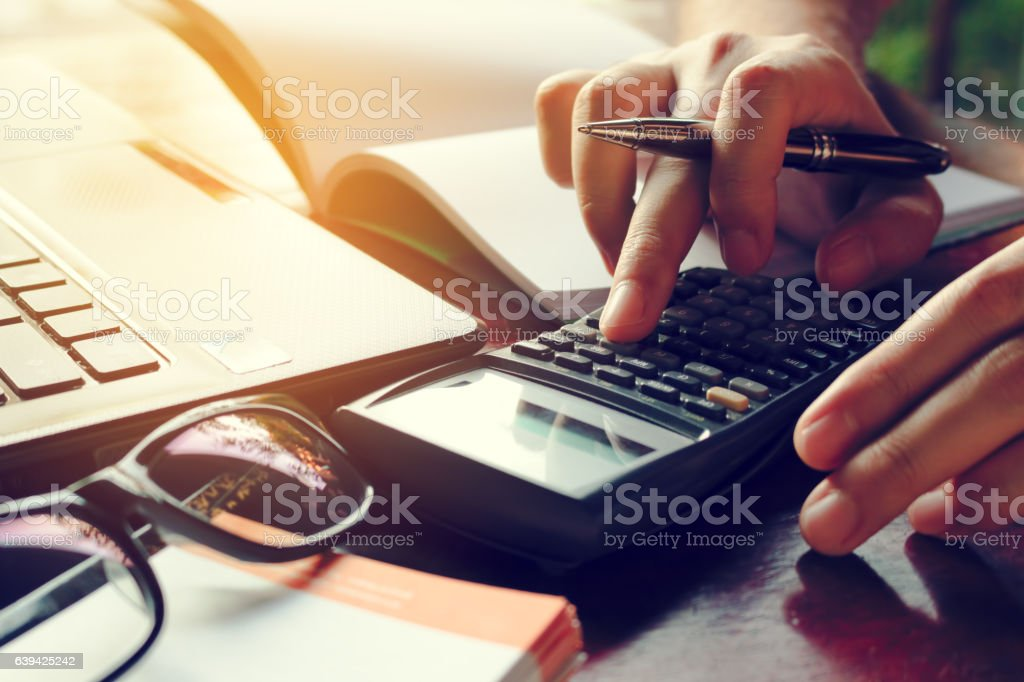 Close up man calculate cost on desk at home. stock photo
