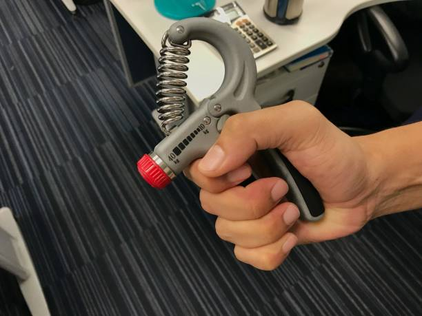 close up man exercise his hand by strength handgrip to prevent office syndrome - hand grip stock photos and pictures