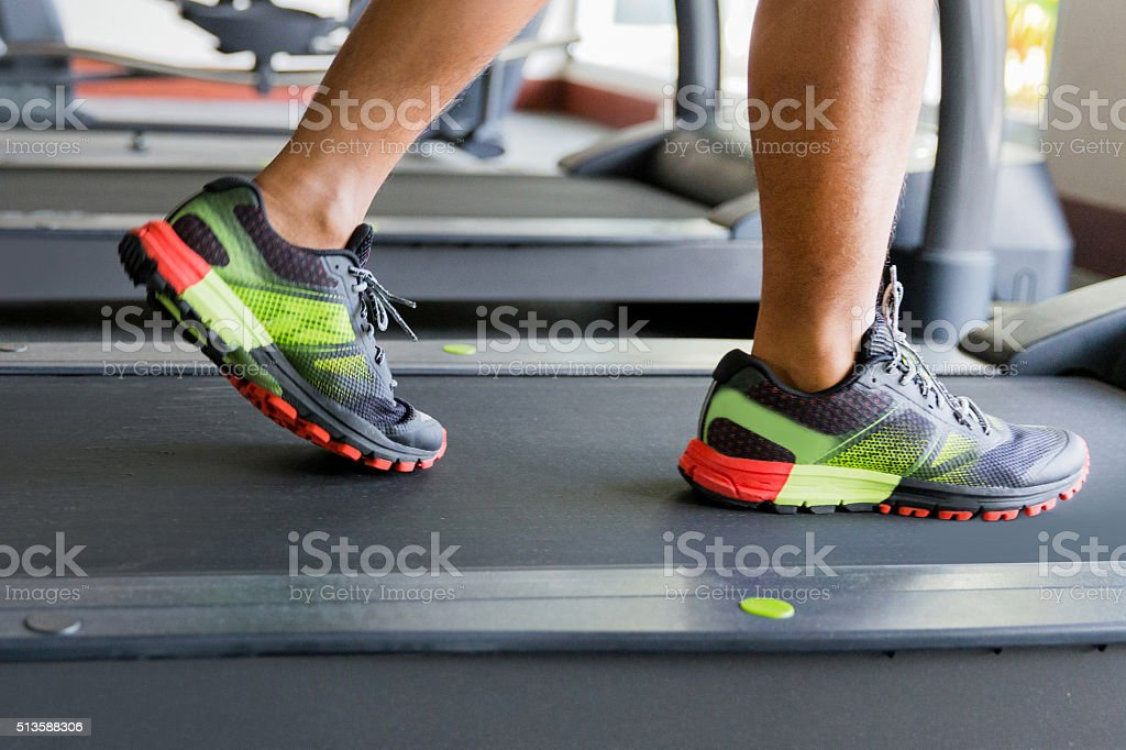 Close up man feet walking on the treadmill stock photo