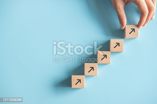 Close up man hand arranging wood block stacking as step stair on paper pink background. Business concept growth success process, copy space.