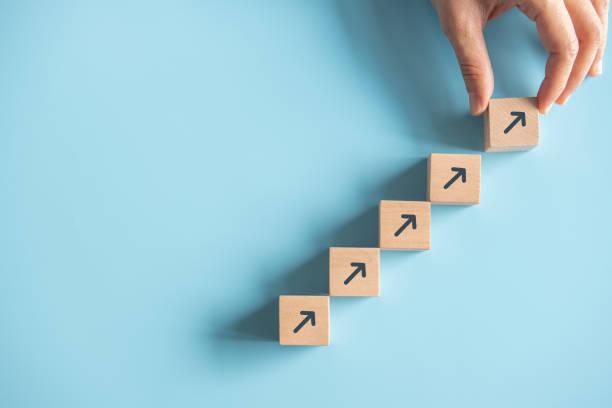 nahaufnahme mann hand arrangieren holzblock stapeln als schritt treppe auf papier rosa hintergrund. geschäftskonzept wachstumserfolgprozess, kopierraum. - fähigkeit stock-fotos und bilder