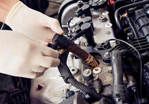 Close up man hand cheking car spark plug