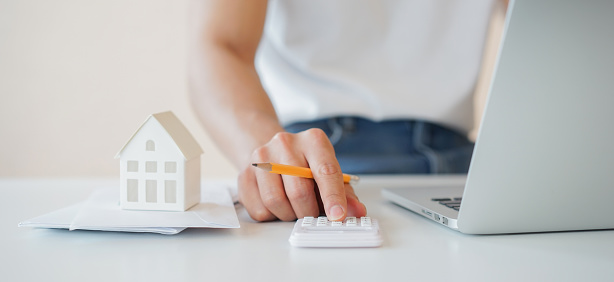 close up man hand counting on calculator with house's model on invoice letter to summary of refinance expense for planning and manage money about home loan mortgage and interest rates for people lifestyle concept
