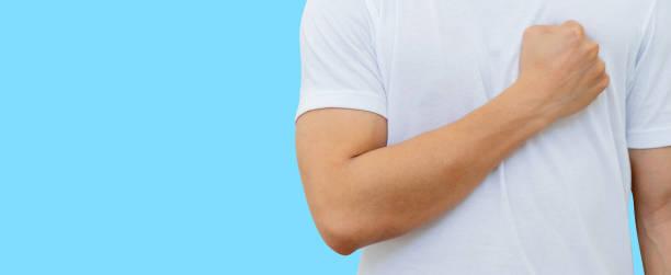 nahaufnahme mann hand geste als faust und berührung auf der brust, um kraft und gute gesundheit isoliert auf blauen farbhintergrund für den weltgesundheitstag und krebs überlebende konzept zu zeigen - immunsystem stärken stock-fotos und bilder