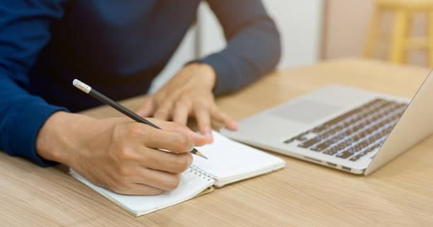 nahaufnahme mann hand mit bleistift und kopie schriftlich form laptop, notizbuch für zusammenfassung über das lernen, onlinekurs, technologie-bildungskonzept - kreatives schreiben übungen stock-fotos und bilder