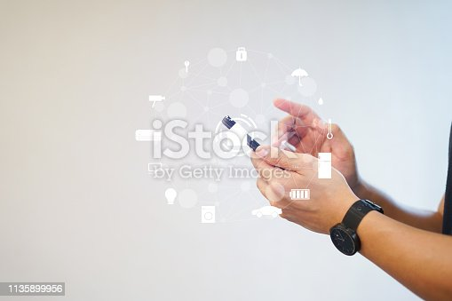 close up man hand holding smartphone for using home automation and turn on monitor function to looking inside or outside home and property , ai innovation future concept