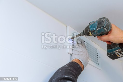 istock Close up man hand installing vent cover from ceiling 1136261310