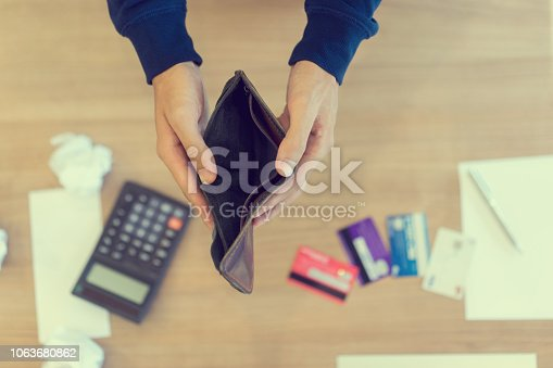 istock close up man hand opening empty wallet over calculator , debt expense bills monthly and credit card at the table in home office ,  managing payroll,money risk financial concept 1063680862