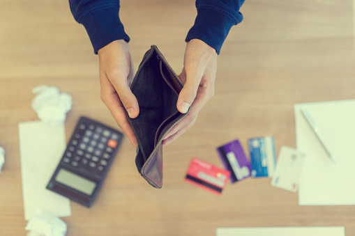 1018458132 istock photo close up man hand opening empty wallet over calculator , debt expense bills monthly and credit card at the table in home office ,  managing payroll,money risk financial concept 1063680862