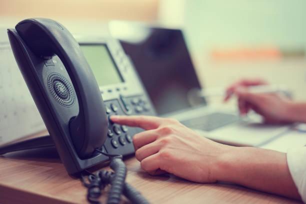 close up man hand point to press button number on telephone office desk.hotline employee concept - cornetta telefono foto e immagini stock