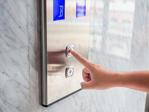 istock Close up man hand press a up button of elevator inside the building for upper high level floor. 1007017354