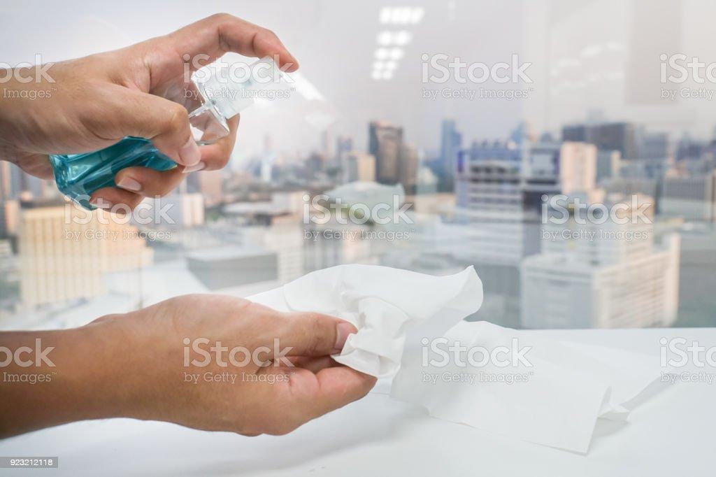 close-up frasco de álcool de uso de mão de homem com papel de seda para sanitários no escritório - foto de acervo