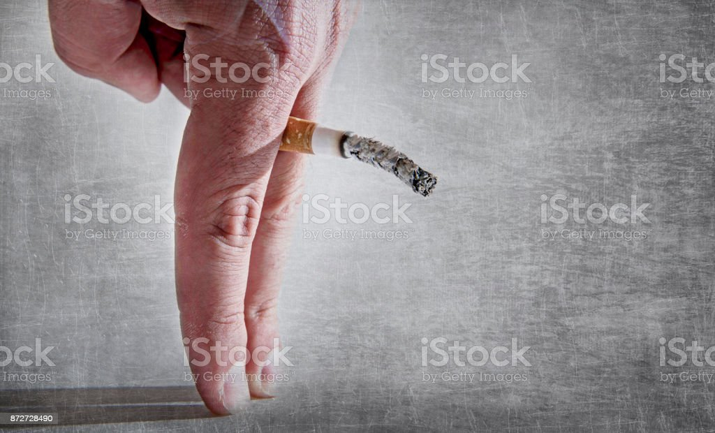 close up man hand with burning cigarette as penis in smoking cause sexual erectile dysfunction and impotence warning concept stock photo