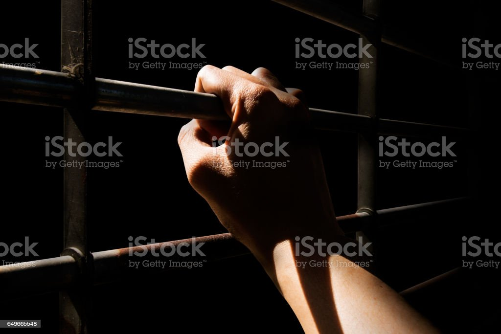 Close up Man hands are holding the cage door in dark room stock photo
