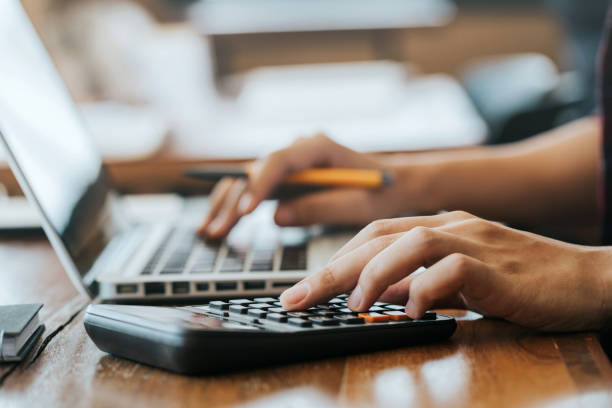 Close up man hands using a calculator and laptop computer for calculating with finance paper, tax, accounting, Accountant concept. Close up man hands using a calculator and laptop computer for calculating with finance paper, tax, accounting, Accountant concept. calculator stock pictures, royalty-free photos & images