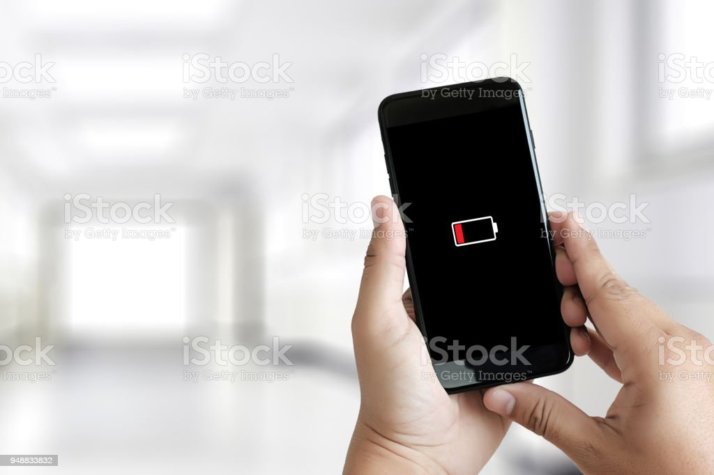 Close up man hands using smart phone battery low charged battery screen stock photo