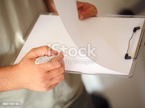 896826068 istock photo close up man hands with pen writing on paper 895769190