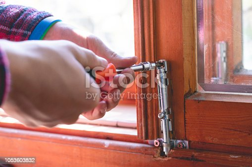 966792200 istock photo close up man hands working adjusting the steel bolt latch on a wooden window f 1053603832