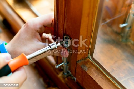 966792200 istock photo close up man hands working adjusting the steel bolt latch on a wooden window f 1053603838