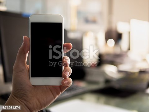 istock Close up man holding and using white smart phone with blank black screen, 871561374