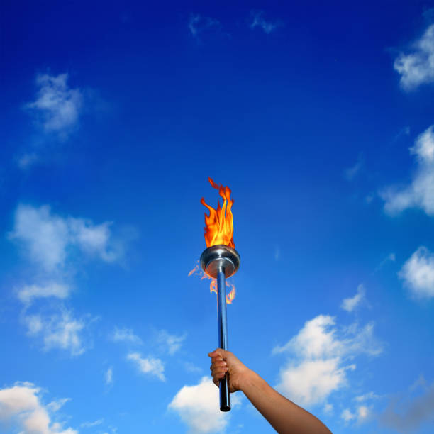 Close up man holding burning flaming torch over cloudy sky Close up of hand holding burning flaming torch over cloudy blue sky flaming torch stock pictures, royalty-free photos & images