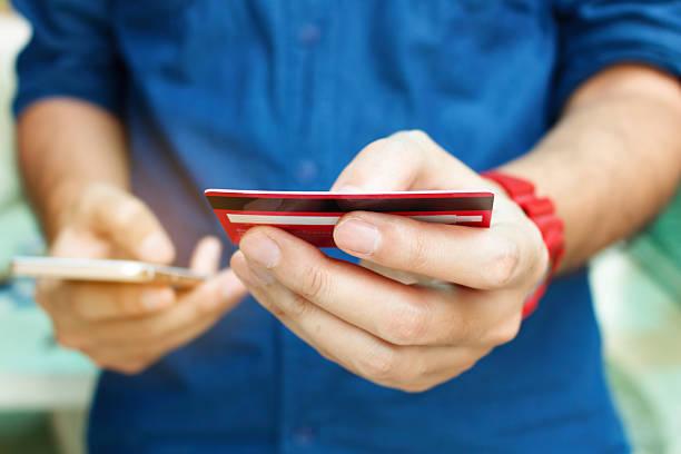close up man holding credit card and use smart phone - iphone gratis stock-fotos und bilder