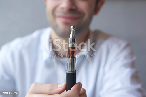 1047058184 istock photo Close up man holding electric cigarette 533032783
