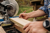 istock close up man measuring boards planks and building wooden patio deck outdoors by his house with circular saw tool 1222750710
