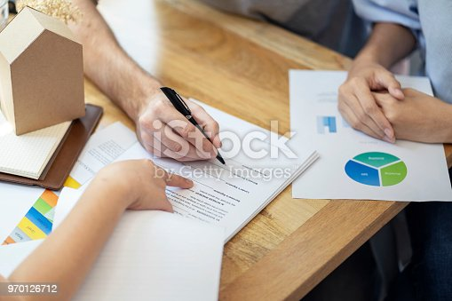 Close up, man putting signature on document loan contract, real estate purchase, hands of woman sale represent point document to sign, contract deals success business.