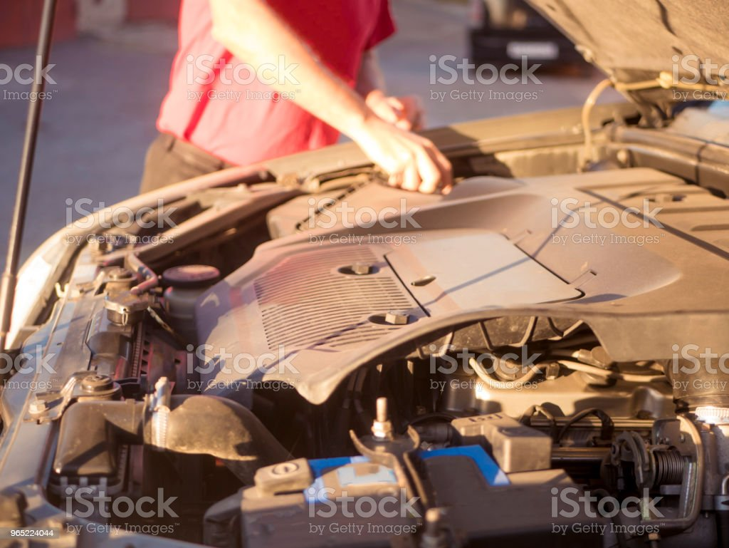 close up man repairing the car with opened hood royalty-free stock photo