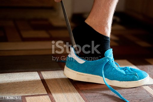 istock close up man try to put on the blue sneaker shoes using the aid 1180867572